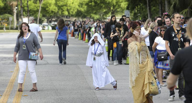 A Star Wars fan, with her daughter dressed as Princess Leia, reacts to seeing the line outside the Orange County Center, in Orlando, Fla., at the 2017 Star Wars Celebration, Thursday, April 13, 2017, marking the 40th anniversary of the original 1977 Star Wars film. Thousands of fans waited for hours in the line, estimated to be more than a mile long, to access the convention. (Joe Burbank/Orlando Sentinel via AP)