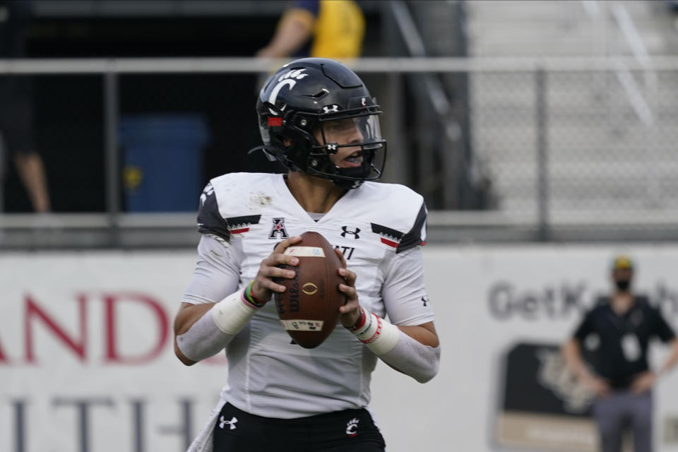 Cincinnati quarterback Desmond Ridder looks for a receiver during the first half of an NCAA college football game, Saturday, Nov. 21, 2020, in Orlando, Fla. (AP Photo/John Raoux)