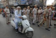 A Muslim man rides a scooter as police officers conduct a flag march in a street outside Jama Masjid, before Supreme Court's verdict on a disputed religious site claimed by both majority Hindus and Muslim in Ayodhya, in the old quarters of Delhi, India, November 9, 2019. REUTERS/Adnan Abidi
