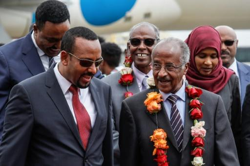 Ethiopia's Prime Minister Abiy Ahmed talks with Eritrea's top diplomat Osman Saleh, wearing a garland, as the two met for a landmark meeting aimed at ending decades of conflict between their two countries