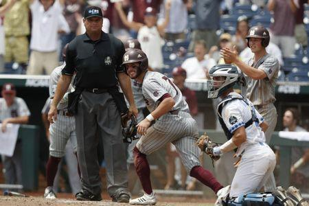 Jun 19, 2018; Omaha, NE, USA; Mississippi State Bulldogs shortstop Luke Alexander (7) scores against North Carolina Tar Heels catcher Brandan Martorano (4) in the eighth inning in the College World Series at TD Ameritrade Park. Mandatory Credit: Bruce Thorson-USA TODAY Sports
