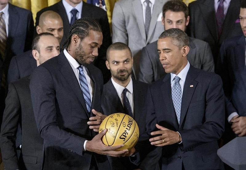 San Antonio Spurs forward Kawhi Leonard (L) hands US President Barack Obama a signed ball during an event in the East Room of the White House January 12, 2015 in Washington, DC. Obama and members of the National Basketball Associations's San Antonio Spurs gathered to celebrate the teams' 2014 NBA championship. AFP PHOTO/BRENDAN SMIALOWSKI (AFP Photo/BRENDAN SMIALOWSKI)