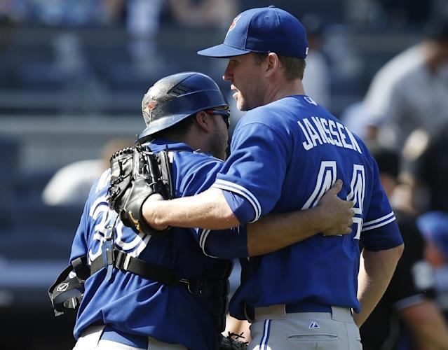 Toronto Blue Jays catcher Dioner Navarro (30) celebrates with Toronto Blue Jays relief pitcher Casey Janssen (44) after Janssen closed out the Blue Jays 5-4 victory over the New York Yankees in a baseball game at Yankee Stadium in New York, Sunday, July 27, 2014. (AP Photo/Kathy Willens)