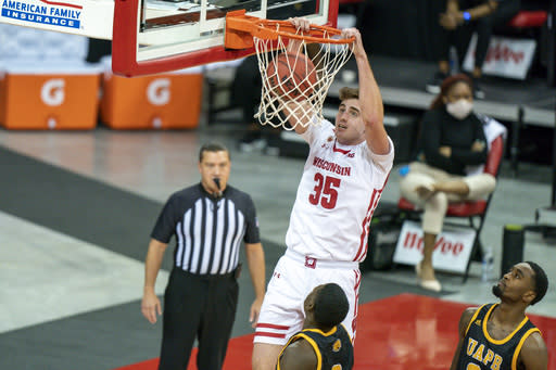 Wisconsin's Nate Reuvers (35) dunks over Arkansas-Pine Bluff's Markedric Bell (3) and Shaun Doss, right, during the first half of an NCAA college basketball game Friday, Nov. 27, 2020, in Madison, Wis. (AP Photo/Andy Manis)