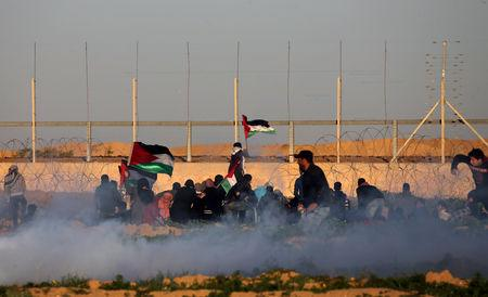 Palestinians protest at the Israel-Gaza border fence as tear gas is fired by Israeli forces, in the southern Gaza Strip January 11, 2019. REUTERS/Ibraheem Abu Mustafa