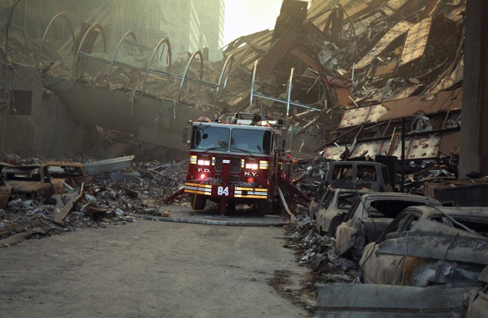 A fire truck is dwarfed by the collapsed structure as it makes its way through the debris. (Caters)