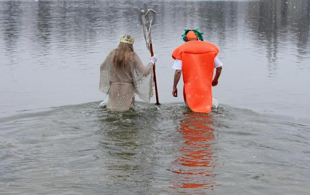 BERLIN, GERMANY - JANUARY 12: Ice swimming enthusiasts dressed as Neptune (L) and a carrot enter the cold waters of Orankesee lake during the 'Winter Swimming in Berlin' event on January 12, 2013 in Berlin, Germany. A local swimmers' group called the 'Berlin Seals' invite ice swimmers from across Germany and abroad to the annual event, which, despite warmer temperatures this winter and a lack of ice, was still held. Members claim ice swimming is good for the body's blood circulation. (Photo by Adam Berry/Getty Images)