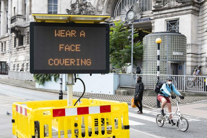 A cyclist wearing a face covering rides past a digital display outside Waterloo Station. (PA)