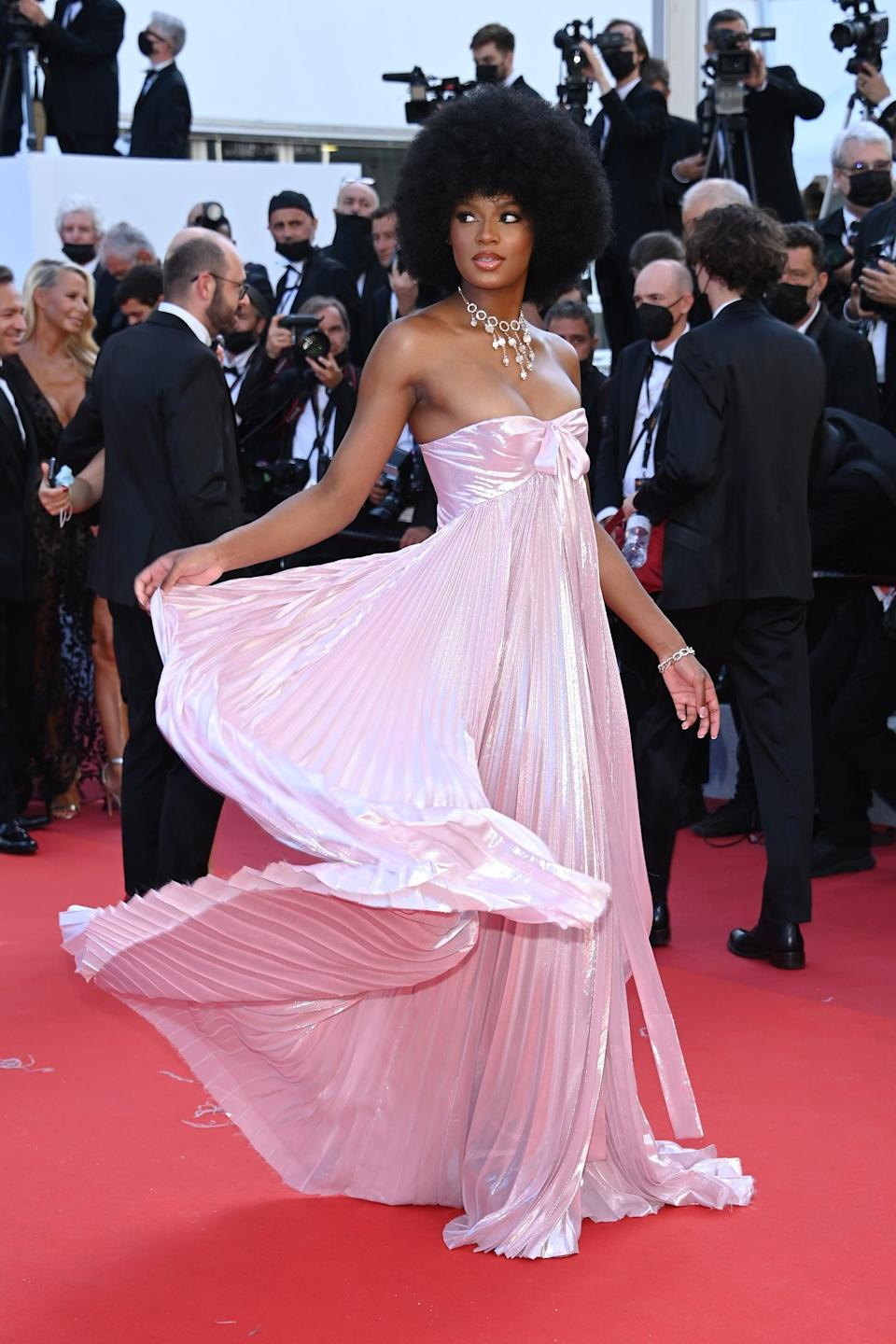<p>Wearing a strapless pink gown.</p>