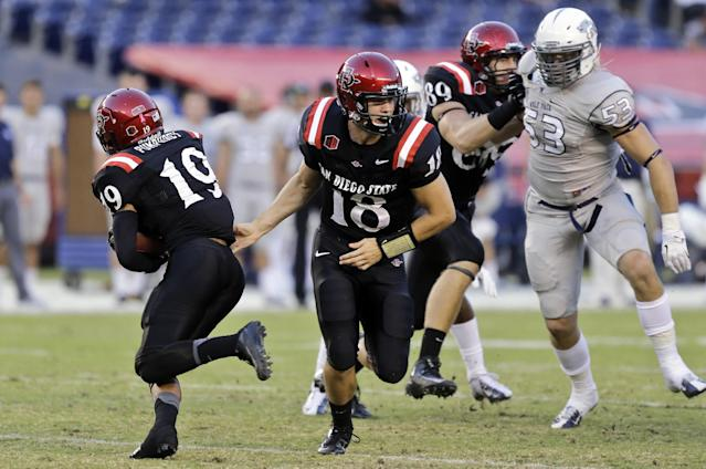 San Diego State quarterback Quinn Kaehler (18) hands the ball to running back Donnel Pumphrey, left, on a reverse as offensive linesman Daniel Brunskill (89) seals off Nevada defensive end Brock Hekking on a 72-yard touchdown run during the first quarter of an NCAA college football game on Friday, Oct. 4, 2013, in San Diego. (AP Photo/Lenny Ignelzi)