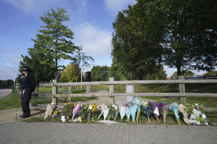 """A police officer stands by floral tributes at Cator Park in Kidbrooke, near to the area where the body of Sabina Nessa was found, in London, Thursday, Sept. 23, 2021. British police investigating the killing of a 28-year-old woman in London say they are probing whether she was attacked by a stranger. It's a case that sparked new concerns for the safety of women walking the capital's streets. Police called for information over the murder of a primary school teacher Sabina Nessa on Sept.17 in southeast London. Detectives believe she was attacked during what would have been a five-minute walk through a local park on her way to meet a friend at the pub. The case came just a few months after the abduction, rape and murder of 33-year-old Sarah Everard in south London by a serving police officer. London Mayor Sadiq Khan described the violence against women as a national """"epidemic."""" (Ian West/PA via AP)"""
