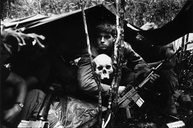 <p>A human skull keeps watch over US soldiers encamped in the Vietnamese jungle during the Vietnam War. (Photo: Terry Fincher/Daily Express/Hulton Archive/Getty Images) </p>