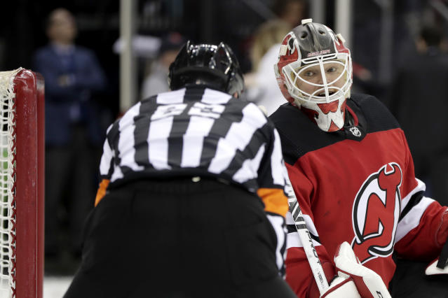 New Jersey Devils goaltender Cory Schneider, right, talks to referee Ghislain Hebert (22) during the third period of an NHL hockey game against the Buffalo Sabres, Monday, March 25, 2019, in Newark, N.J. The Devils won 3-1. (AP Photo/Julio Cortez)