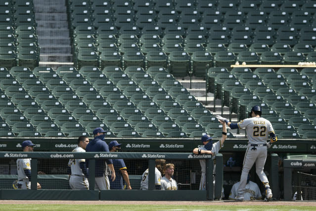 Milwaukee Brewers' Christian Yelich (22) celebrates with manager Craig Counsell at the dugout after hitting a two-run home run during the sixth inning of a baseball game against the Chicago Cubs, Saturday, July 25, 2020, in Chicago. (AP Photo/Paul Beaty)