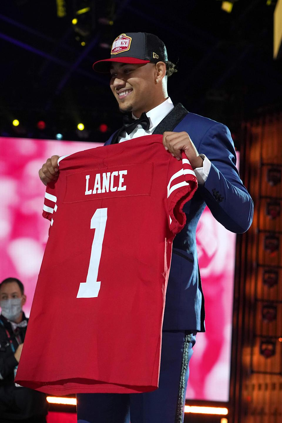 Trey Lance poses with a jersey after being selected as the third pick by the San Francisco 49ers.