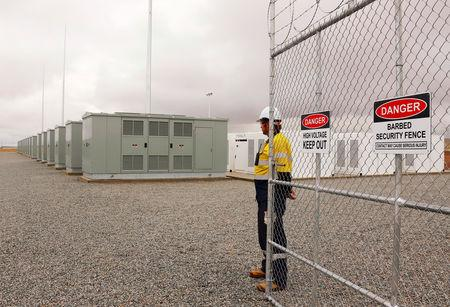FILE PHOTO:    A worker stands at the main gate for the compound housing the Hornsdale Power Reserve, featuring the world's largest lithium ion battery made by Tesla, during the official launch near the South Australian town of Jamestown, in Australia, December 1, 2017.      REUTERS/David Gray/File Photo