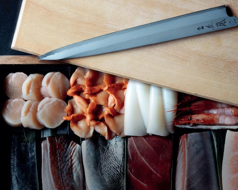 A array of sashimi with a wooden chopping board and Japanese knife