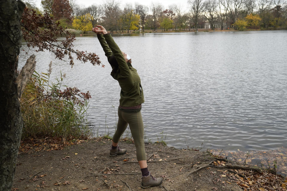 Writer, musician actor and singer Lori Brigantino stretches during a stop while riding her bicycle through the peninsula on the lake in Prospect Park, Sunday, Nov. 15, 2020, in the Brooklyn borough of New York. (AP Photo/Kathy Willens)