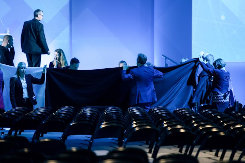 29 October 2019, North Rhine-Westphalia, Dortmund: Helpers shield the view to the stage with a blanket after Economics Minister Peter Altmaier (CDU) fell heavily at the digital summit. After his opening speech at the Digital Summit in Dortmund, Altmaier fell off the stage while walking. Photo: Bernd Thissen/dpa (Photo by Bernd Thissen/picture alliance via Getty Images)
