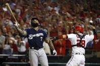 Milwaukee Brewers' Eric Thames, left, flips his bat after striking out in front of Washington Nationals catcher Kurt Suzuki in the ninth inning of a National League wild-card baseball game, Tuesday, Oct. 1, 2019, in Washington. Washington won 4-3. (AP Photo/Patrick Semansky)