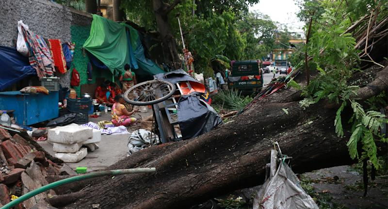 Fallen trees, an overturned cart and a mess of debris on a street in Kolkata, India, on May 21. Source: AAP