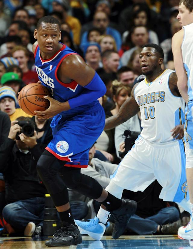 Philadelphia 76ers center Lavoy Allen, left, picks up a loose ball as Denver Nuggets guard Nate Robinson covers in the fourth quarter of the Sixers' 114-102 victory in an NBA basketball game in Denver on Wednesday, Jan. 1, 2014. (AP Photo/David Zalubowski)