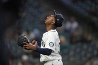 Seattle Mariners starting pitcher Justin Dunn motions and looks skyward as he comes off the field after being removed during the sixth inning of the team's baseball game against the Texas Rangers on Saturday, May 29, 2021, in Seattle. (AP Photo/Elaine Thompson)