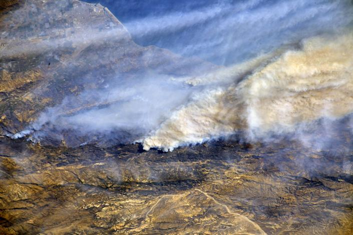 <p>From a Dec. 8, 2017, International Space Station flyover of Southern California, NASA astronaut Randy Bresnik photographed the plumes of smoke rising from wildfires. (Photo: NASA) </p>