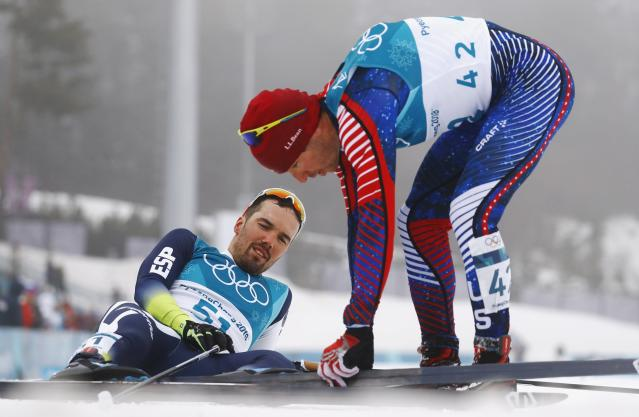 Cross-Country Skiing - Pyeongchang 2018 Winter Olympics - Men's 50km Mass Start Classic - Alpensia Cross-Country Skiing Centre - Pyeongchang, South Korea - February 24, 2018 - Imanol Rojo of Spain and Noah Hoffman of the U.S. react at the finish line after the race. REUTERS/Kai Pfaffenbach