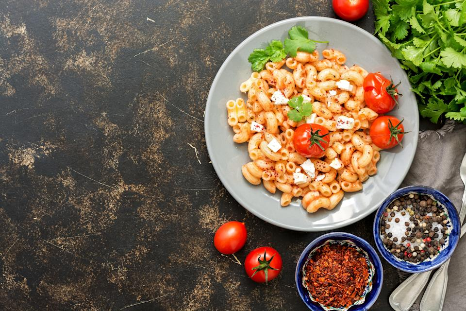 Pasta with feta cheese, sauce and baked tomatoes. Italian dish. Dark background, flat lay