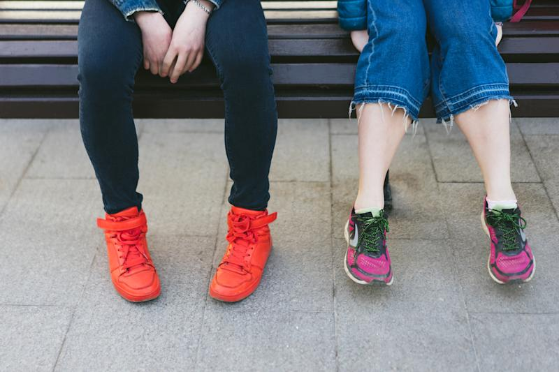 male and female legs in bright sneakers are sitting on a bench
