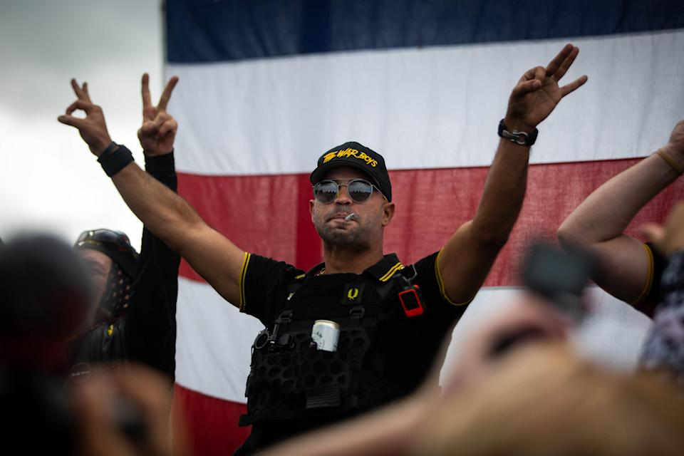 """Enrique Tarrio flashes the """"OK"""" sign, sometimes used as a symbol of white supremacy, as hundreds gather during a Proud Boys rally at Delta Park in Portland, Ore., on Sept. 26, 2020, to show support for President Donald Trump and condemn violence during Black Lives Matter and antifa protests."""