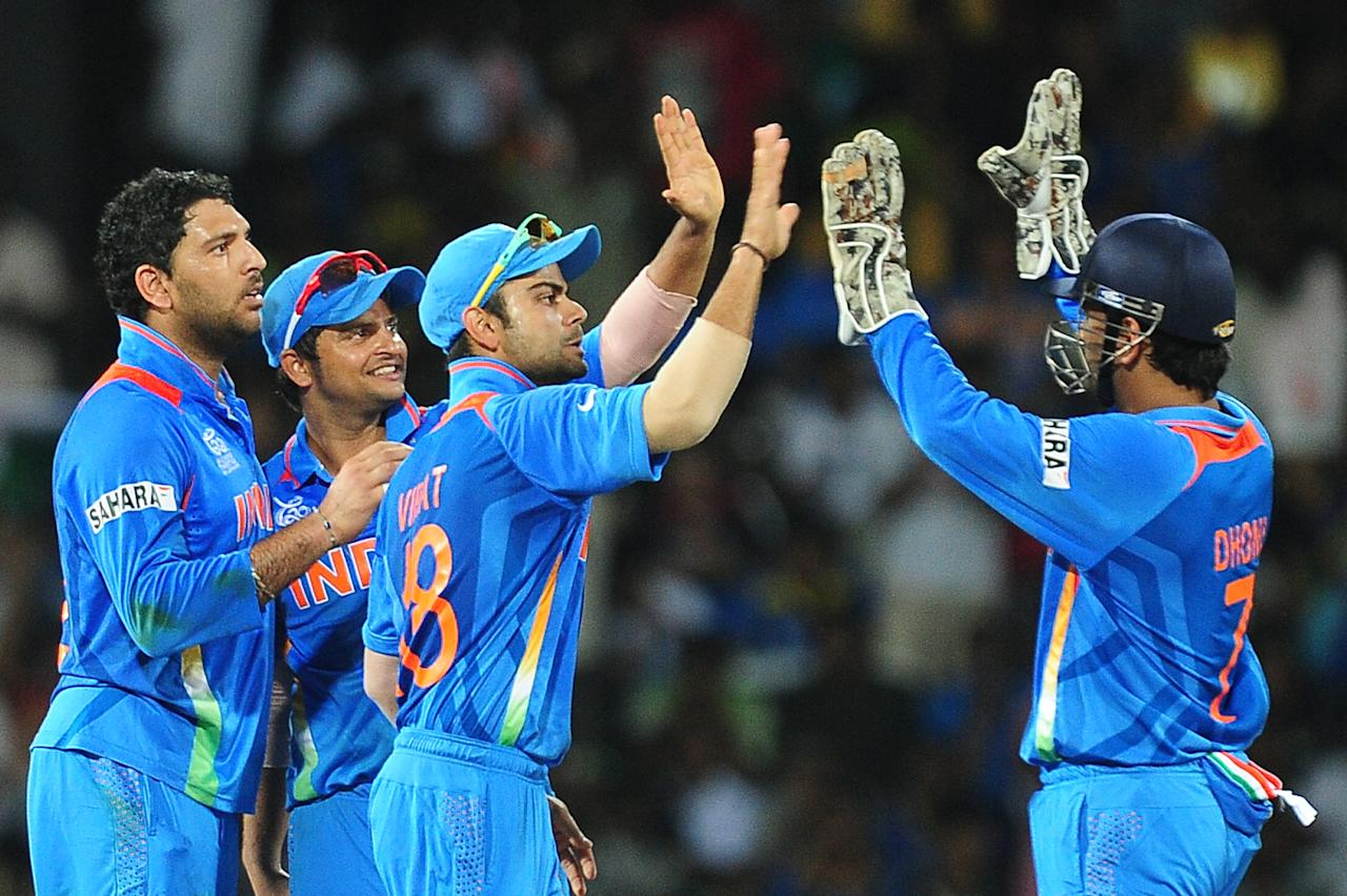 Indian cricketer Yuvraj Singh (L) celebrates with his teammates after he dismissed  Pakistan batsman Nasir Jamshed during the ICC Twenty20 Cricket World Cup's Super Eight match between India and Pakistan at the R. Premadasa International Cricket Stadium in Colombo on September 30, 2012. AFP PHOTO/ LAKRUWAN WANNIARACHCHI