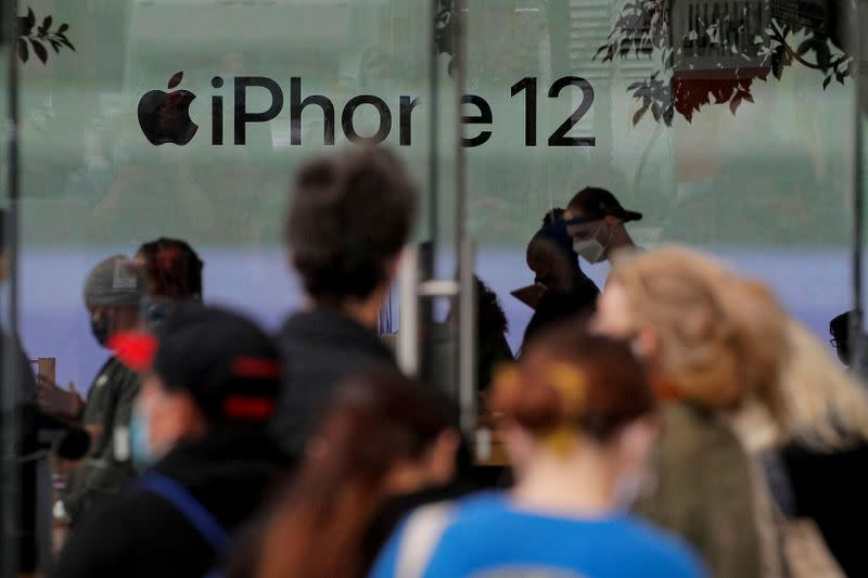 FILE PHOTO: Customers wait in line outside an Apple Store to pick up Apple's new 5G iPhone 12 in Brooklyn, New York