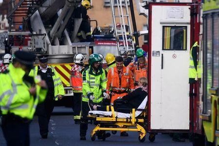 Emergency personnel rescue a woman trapped on the top floor of a bus after it crashed into a shop on Lavender Hill in Clapham, London, Britain August 10, 2017. REUTERS/Dylan Martinez