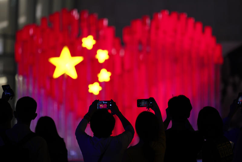 Visitors take photos with their smart phones of an installation depicting a heart shape Chinese national flag in Shanghai, China, Friday, Sept. 27, 2019. China will mark its 70th anniversary on Oct. 1, 2019. (AP Photo)