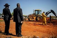 A relative and a pastor stand by as a mechanical digger moves in to cover the grave