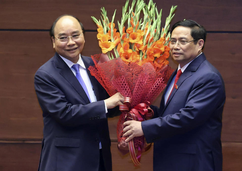 Vietnamese newly elected President Nguyen Xuan Phuc, left, and newly elected Prime Minister Pham Minh Chinh pose for a photo in the National Assembly in Hanoi, Vietnam on Monday, April 5, 2021. Vietnam's legislature voted Monday to make Pham Minh Chinh, a member of the Communist party's central committee for personnel and organization, the country's next prime minister. Outgoing Prime Minister Nguyen Xuan Phuc was appointed the new president. (Hoang Thong Nhat/VNA via AP)