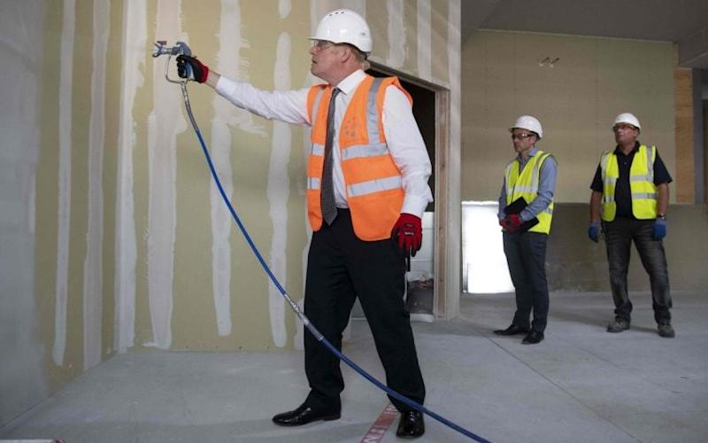 The PM helped on a construction site yesterday - but warned of a long way to 'economic vitality' - MATTHEW HORWOOD/AFP