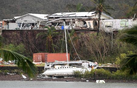 A damaged building is seen behind a boat that was pushed onto a bank due to Cyclone Debbie in the township of Airlie Beach, located south of the northern Australian city of Townsville