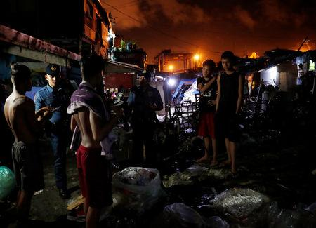 Police officers interrogate teenagers after they are rounded up lingering in the streets of Tondo, Manila, Philippines July 2, 2018. REUTERS/Erik De Castro/Files