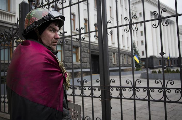 A protester stands in front of presidential administrative building in central Kiev, Ukraine, Saturday, Feb. 22, 2014. Protesters in the Ukrainian capital claimed full control of the city Saturday following the signing of a Western-brokered peace deal aimed at ending the nation's three-month political crisis. The nation's embattled president, Viktor Yanukovych, reportedly had fled the capital for his support base in Ukraine's Russia-leaning east. (AP Photo/Darko Bandic)