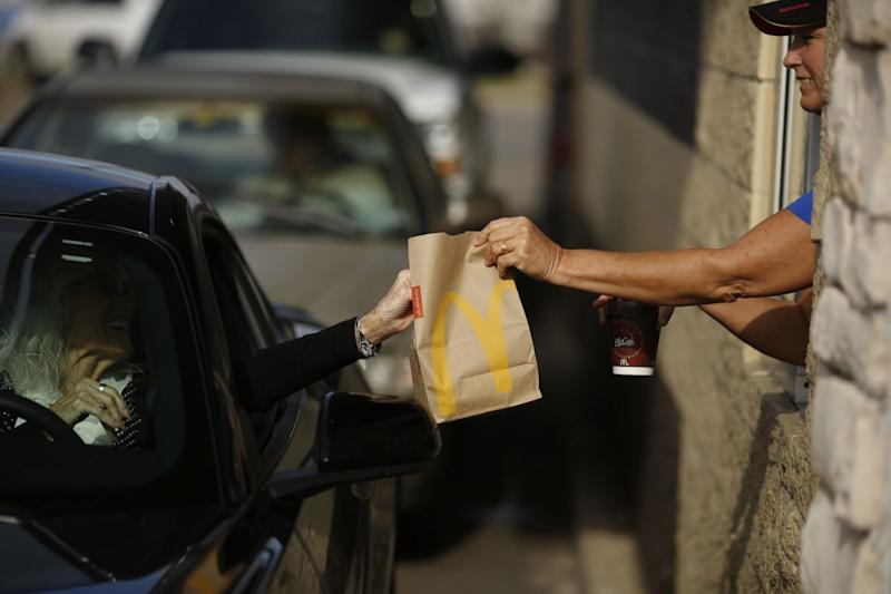 A McDonald's worker passes a woman a bag of food from the drive-thru window.