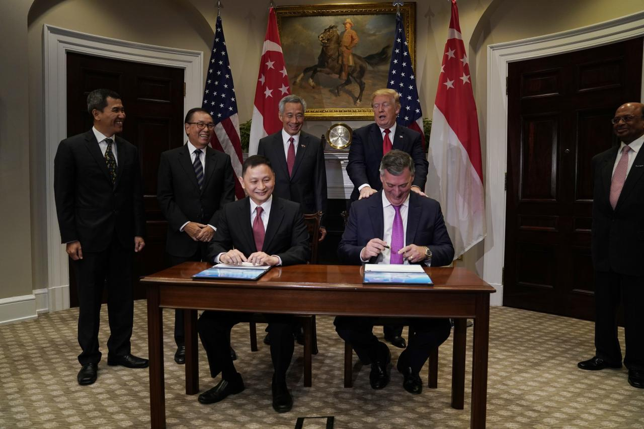 U.S. President Donald Trump and Singapore's Prime Minister Lee Hsien Loong join Singapore Airlines CEO Goh Choon Phong and Boeing's commercial airplanes CEO Kevin McAllister as they sign a sales contract for planes in the Roosevelt Room at the White House in Washington, U.S. October 23, 2017. REUTERS/Jonathan Ernst