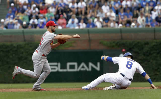 St. Louis Cardinals' Paul DeJong, left, turns the double play after forcing Chicago Cubs' Ian Happ at second and getting Jason Heyward at first during the first inning of a baseball game Saturday, July 21, 2018, in Chicago. (AP Photo/Charles Rex Arbogast)