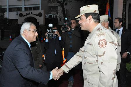 Egypt's interim President Adly Mansour (L) shakes hands with Egypt's army chief Field Marshal Abdel Fattah al-Sisi (R), after his meeting with members of the Supreme Council of the Armed Forces, in Cairo March 26, 2014. REUTERS/Egyptian Ministry of Defence/Handout