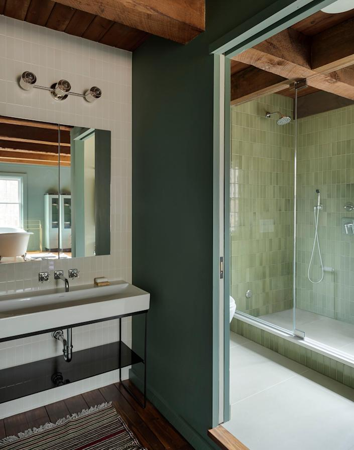 AFTER: The soothing green color in the main bathroom creates an elegant and relaxing environment.