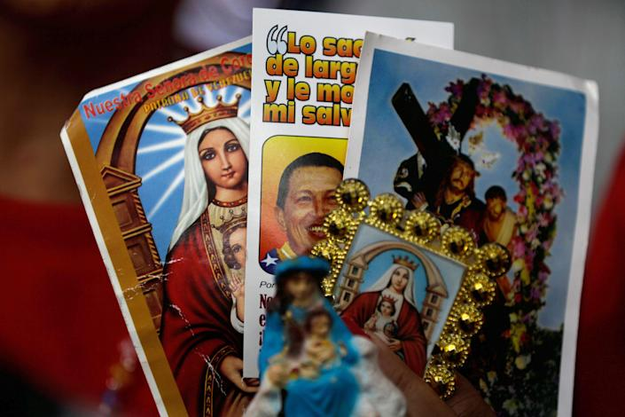 """A person holds up an image of Venezuela's President Hugo Chavez among religious images during a demonstration in support of him at the Simon Bolivar square in Caracas, Venezuela, Sunday Dec. 9, 2012. Chavez was heading back to Cuba on Sunday for more cancer surgery after announcing that the illness returned despite two previous operations, chemotherapy and radiation treatment. Chavez said Saturday that if there are """"circumstances that prevent me from exercising the presidency further"""" Vice-President Nicolas Maduro should replace him for the remainder of his term. (AP Photo/Fernando Llano)"""