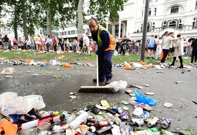 A worker clears rubbish left by fans at Leicester Square, London before the UEFA Euro 2020 Final between Italy and England