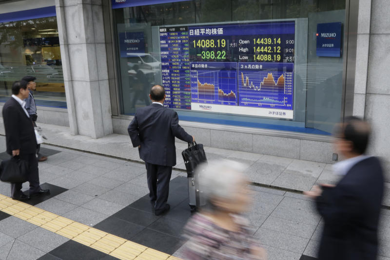Pedestrians look at an electronic stock indicator showing Japan's Nikkei 225 shed 398.22 points, or 2.7 percent, to 14,088.19 in Tokyo Friday, Oct. 25, 2013. Asian stock markets were dragged down Friday by doubts about the durability of recoveries in China and Japan, the region's two biggest economies. (AP Photo/Shizuo Kambayashi)